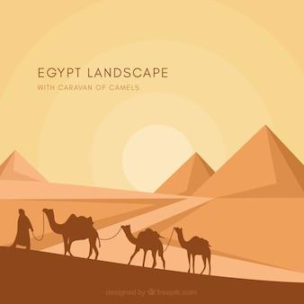 ラクダのキャラバンとエジプトのピラミッドの風景の背景