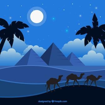 낙타의 캐러밴과 이집트 피라미드 밤 풍경의 배경