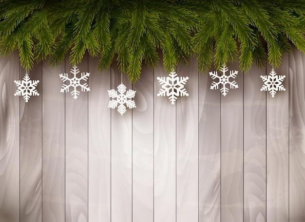 木製の壁の前にクリスマスツリーの枝と雪片の背景。ベクター。