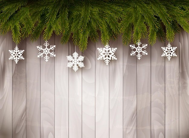 Background with christmas tree branches and snowflakes in front of a wooden wall. vector.