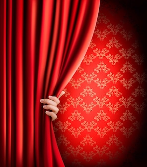赤いベルベットのカーテンと手で背景。