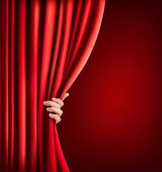 赤いベルベットのカーテンと手で背景