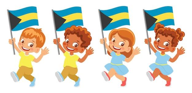 Флаг багамских островов в руке. дети держат флаг. государственный флаг багамских островов