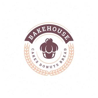 パン屋のバッジまたはラベルのレトロなイラストのカップケーキとパン屋の小麦のシルエット。