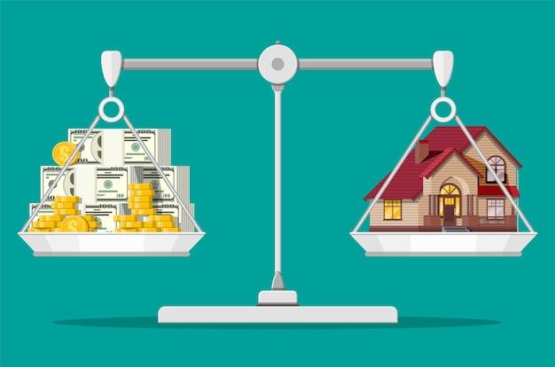 Весы балансируют с частным домом и деньгами. покупка дома. недвижимость. пригородный деревянный дом, долларовые стеки и золотые монеты.