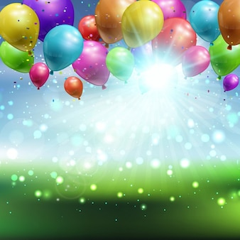 Balloons and confetti on a defocussed landscape background