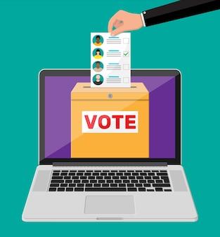 投票箱、ノートパソコンの画面に候補者を記載した文書。選挙法案を手に。顔のある紙に投票してください。