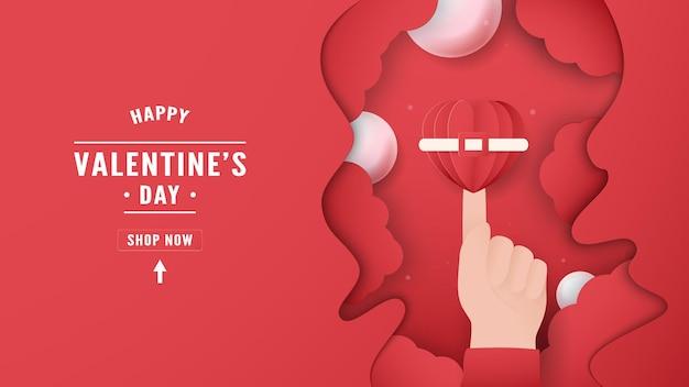 バレンタインデーのバナー。手が心に触れる。テキストスペースは左側にあります。イラストはペーパーカット風です。