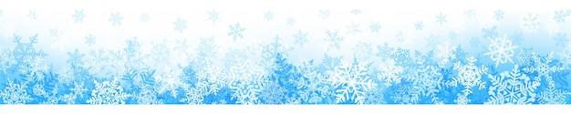 水色のシームレスな水平方向の繰り返しを持つ複雑なクリスマスの雪片のバナー。雪が降る冬の背景