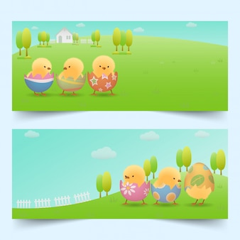 Banners set of yellow chicks in cracked easter eggs on green slope