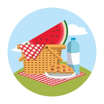 Basket with watermelon and water bottle in the tablecloth