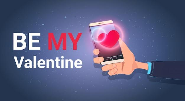 Рука держа смартфон с be my valentine текстовое сообщение love holiday празднование приглашение