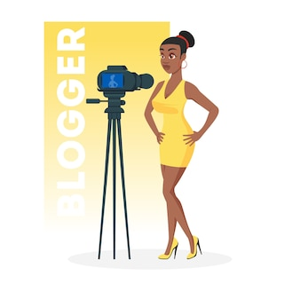 三脚にカメラの前に立っているミニ黄色のドレスを着た美しいアフリカ系アメリカ人の女の子。ファッションvlog、ライブチュートリアルビデオ、インタビューを記録するセクシーなアフリカの女性。