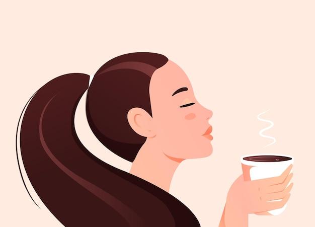 朝の味のコーヒーのカップを保持している美しい少女