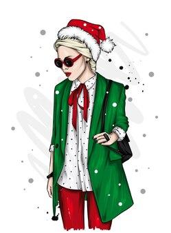 スタイリッシュなクリスマスの服とサンタクロースと新年の帽子の美しい少女