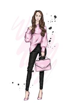 スタイリッシュな服のファッションとアクセサリーの美しい女の子