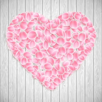 Beautiful heart made from pink sakura petals on wooden texture.