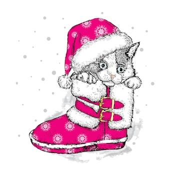 クリスマスの帽子とブーツの美しい子猫