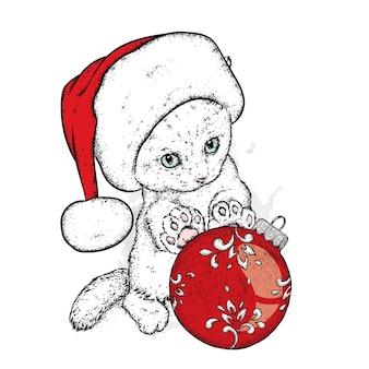 クリスマスの帽子とボールを持つ美しい子猫。