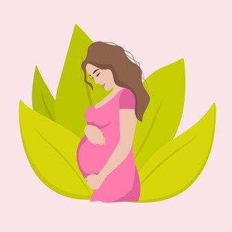 Красивая беременная женщина с большим животом улыбается на фоне листьев.