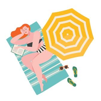Красивая красная женщина в полосатом бикини, лежа, загорая, спит с книгой на пляже