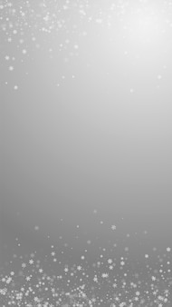 Beautiful snowfall christmas background. subtle flying snow flakes and stars on grey background. admirable winter silver snowflake overlay template. quaint vertical illustration.