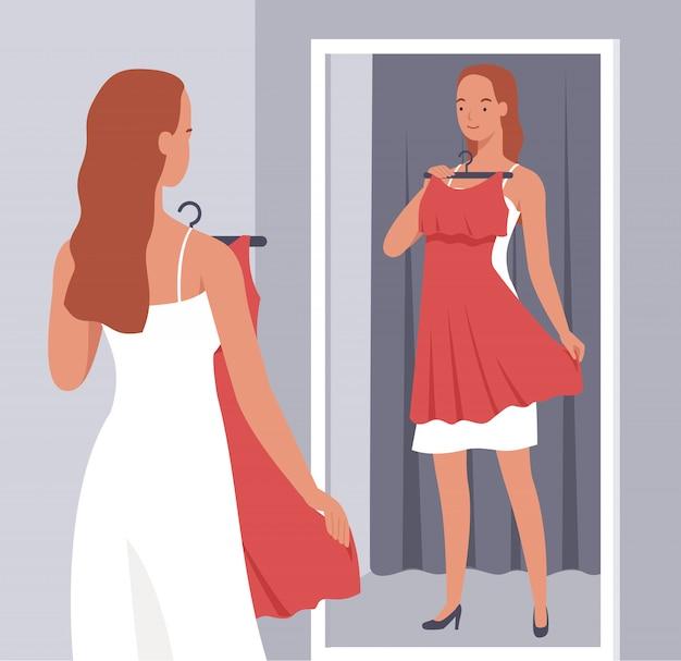 Красивая женщина примеряет красное платье перед зеркалом в примерочной.
