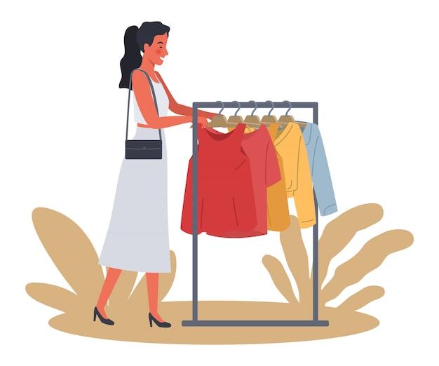 美しい女性のショッピング。若い女性は服を買うことを選びます。
