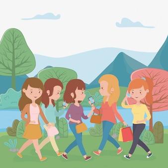 Belle donne che camminano nel parco utilizzando gli smartphone