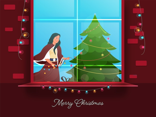 Beautiful young girl decorated xmas tree from lighting garland with window on red background for merry christmas celebration.