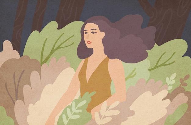 緑の茂みの間に立っている風に手を振っている長いブルネットの髪を持つ美しい若い女性。