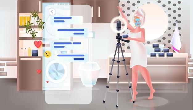 三脚のブログの概念の完全な長さの水平方向のベクトル図にカメラでオンラインビデオを記録するトレンドメイクチュートリアルを示すマスクの女性を適用する美容ブロガー