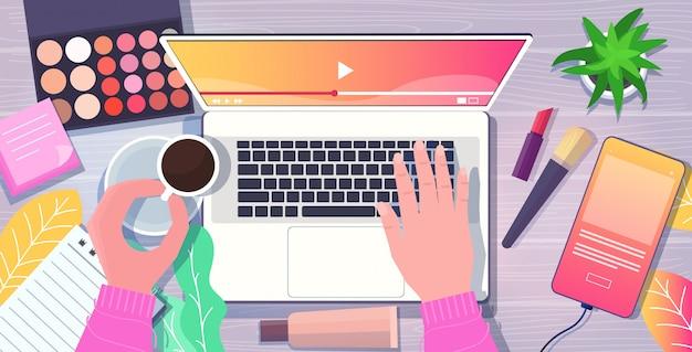 職場のラップトップを使用して美容ブロガーの手スマートフォン化粧品コーヒーカップデスクソーシャルメディアネットワークブログコンセプトトップアングルビュー水平図