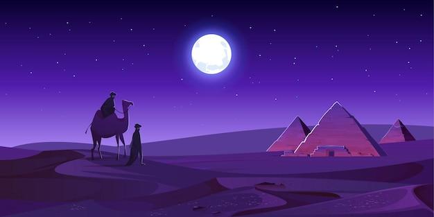 베두인들은 밤 사막에서 낙타를 타고 이집트 피라미드로 걸어갑니다.