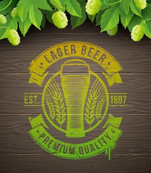 Beer emblem painted on wooden surface and ripe hops and leaves