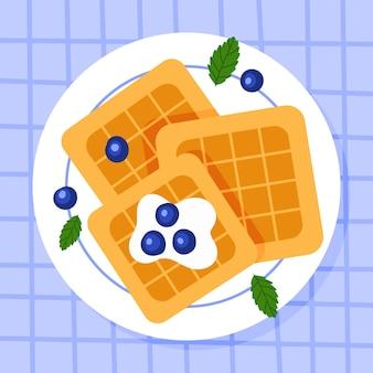 皿にブルーベリーとミントを添えたベルギーのワッフル。朝ごはん。