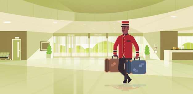 スーツケースホテルサービスコンセプトアフリカ系アメリカ人のベルマンが均一なモダンなレセプションエリアのロビーのインテリアで荷物の男性労働者を保持しているベルの少年