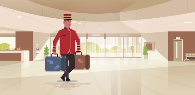 スーツケースを運ぶベル少年ホテルサービスコンセプトベルマンは均一なモダンなレセプションエリアのロビーのインテリアで荷物の男性労働者を保持