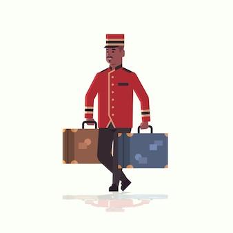 Колокол мальчик нося чемоданы концепция обслуживания афроамериканец bellman держа багаж мужской работник гостиницы в форме