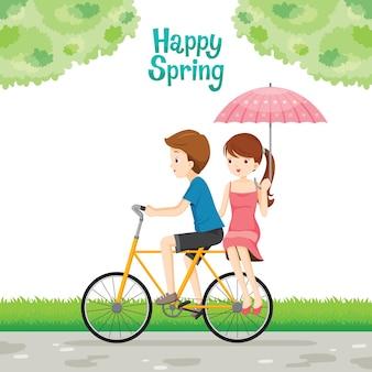 Велосипедист мужчина и женщина с зонтиком, сидящие сзади