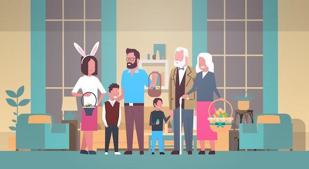 Большая семья празднует счастливую пасху, держа корзину с яйцами и уши кролика над домашним интерьером
