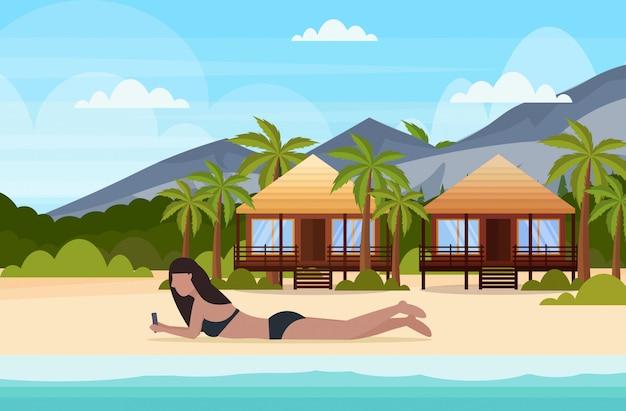 Bikini woman sunbathing girl in swimsuit using smartphone social media communication summer vacation concept bunglow house landscape background full length horizontal