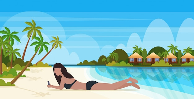 Bikini woman sunbathing girl in swimsuit using smartphone social media communication summer vacation concept bunglow house landscape background full length horizontal
