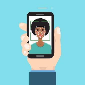 生体認証、顔認識システムのコンセプト。手にスマートフォン。