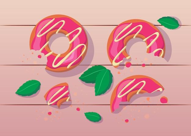 白いアイシングのイラストとかまれて半分食べられたピンクのドーナツ