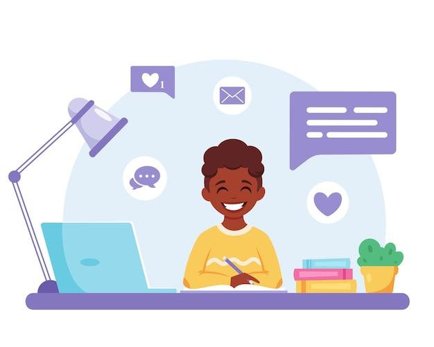 学校に戻って勉強しているコンピュータオンラインで勉強している黒人の少年