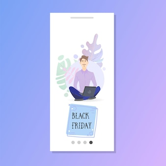 Black friday online ordering man with laptop in lotus position in the park