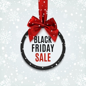Black friday round banner with red ribbon and bow, on winter background with snow and snowflakes. brochure or banner template.