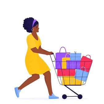 검은 금요일 판매 배너. 아프리카 계 미국인 여자는 구매 및 선물로 가득한 트롤리로 쇼핑하고 있습니다.