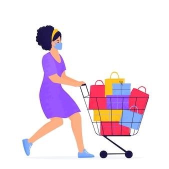 검은 금요일 판매 배너. 안면 보호 마스크를 쓴 소녀가 구매 및 선물로 가득 찬 트롤리로 쇼핑하고 있습니다.